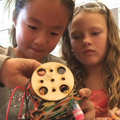 Girls inventing in classroom